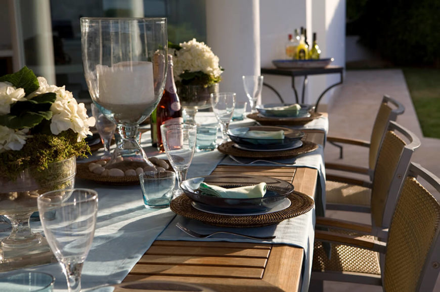 A table set for an outdoor dinner party. Light blue placemats match the table runner perfectly. Wicker plate holders fit around the salad plate, topped by a translucent gray bowl. A wine glass and a small water tumbler are above the plates.