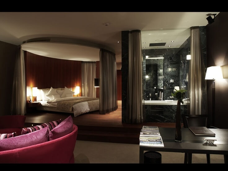 A luxurious primary suite with a marble jacuzzi that can be hidden behind drawn curtains. Curtains can also be drawn around the bed platform. To the left is a large curved sofa in red-pink.
