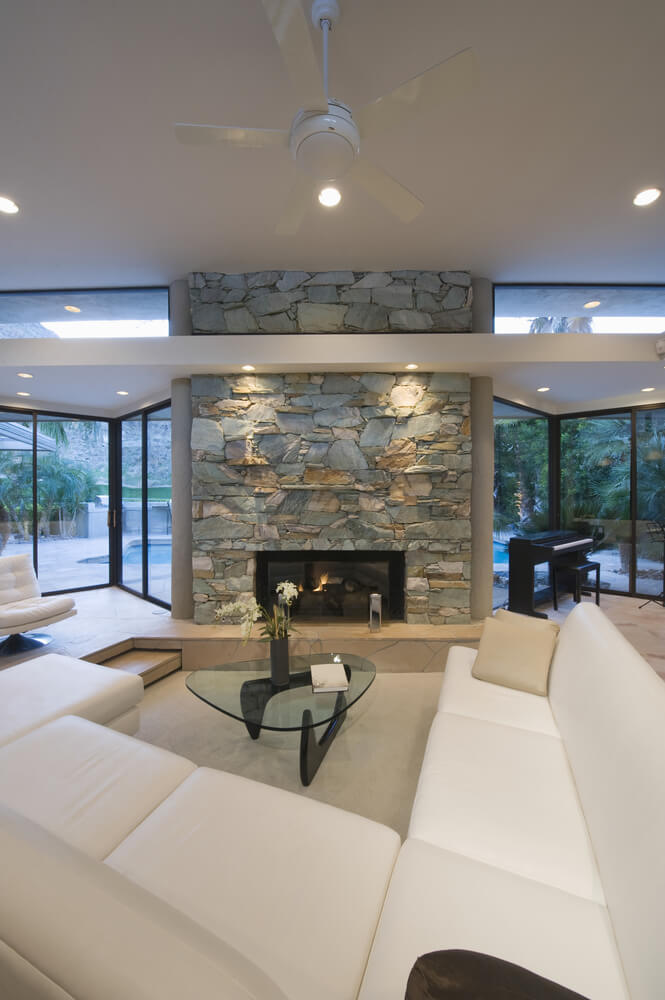 A much more modern living room with a multi-tone stone fireplace. The glass-enclosed fireplace rests low to the raised hearth. The main seating area is in a shallow pit in the floor, allowing the fireplace to seem much taller.