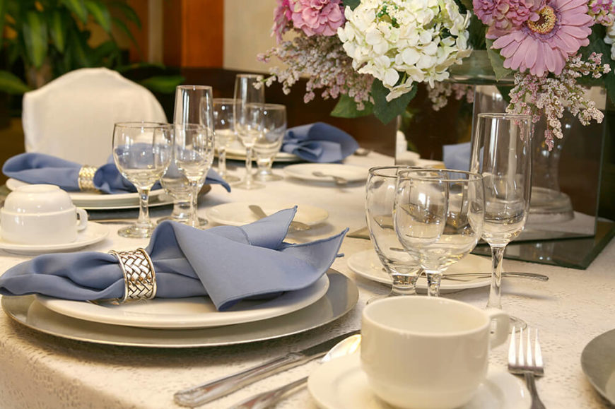 Simple white place setting with three wine glasses and a coffee cup on a eyelet lace tablecloth. At the center of each plate is a periwinkle napkin in a silver napkin ring.