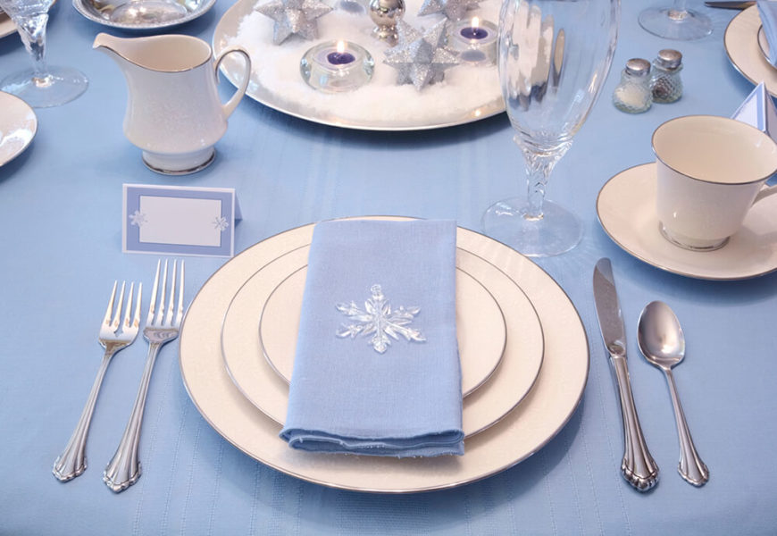A winter-themed place setting with silver-rimmed dishes and a single wine glass. Small paper place cards are trimmed with small snowflakes, and the simply folded napkin at the center of each place setting is topped by a crystal snowflake.