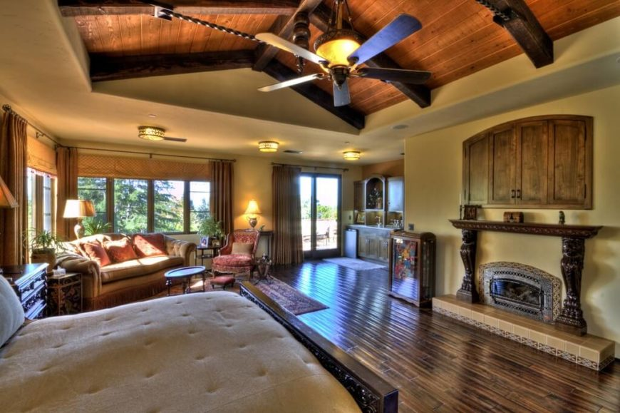 An enormous master bedroom suite with tons of windows and a vaulted ceiling. Near the sliding glass doors that lead outside is a small kitchenette.