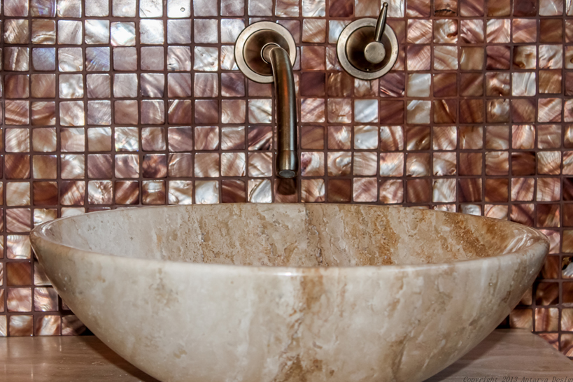 This close-up of the powder room sink shows the luxurious marble vessel sink and brushed nickel fixtures against the bronze tile.