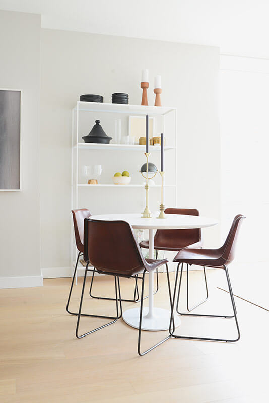 The dining table set perfectly centers the open-plan space, encompassing elements from throughout the interior in a minimalist fashion. A white bookshelf standing against the wall holds nicknacks and art pieces, adding detail and color to the room.