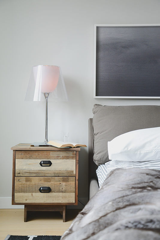 The bedroom boasts an abundance of unique elements, including the rustic wood bedside dresser and accompanying lamp, with a chromed body and transparent shade.