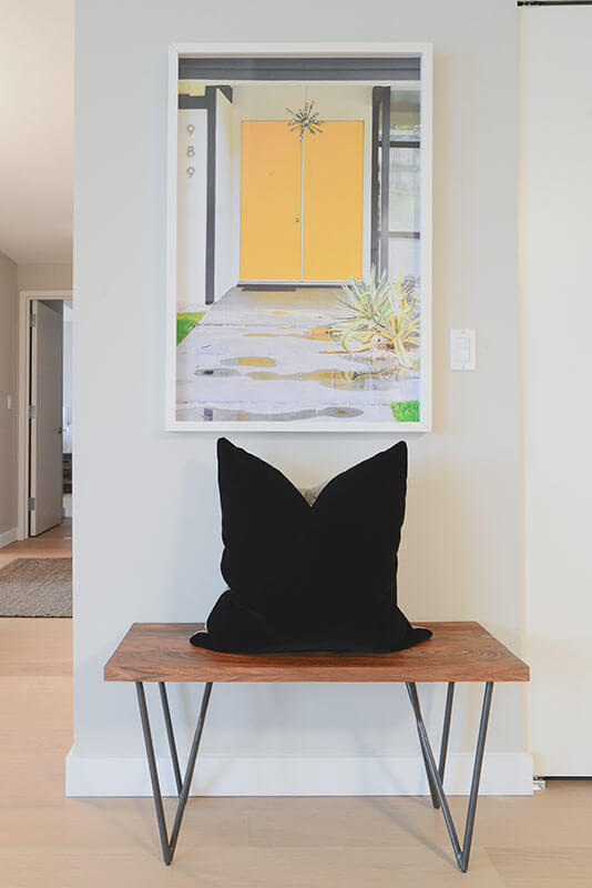 In the hallway, the playful sense of detail and scope flourishes. Here we see another minimalist furniture piece, a bench with rustic wood top and metal wire framing, standing below a bright and colorful painting.