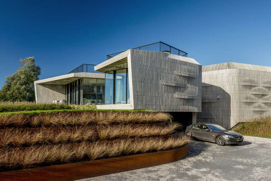 The home's garage is tucked beneath one of the four wings of the house, below the main floor. The driveway is rimmed by terraces of grasses that lead up to the lush green yard.