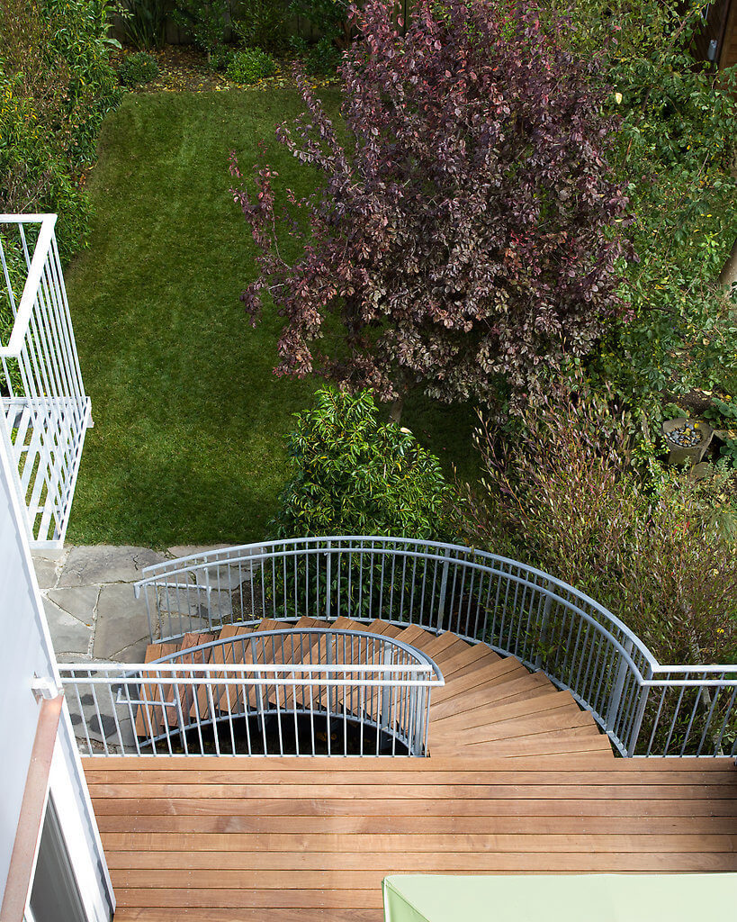 Exiting the house, into the backyard, you see the attractive stain of the outside deck and staircase, encased by metal railings, all leading out to a gorgeous yard.