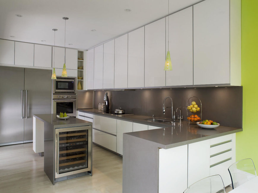 From the other end of the kitchen, the polished steel appliances becomes evident and works well with the slate grey of the counter's backing along with the integrated wine cooler.
