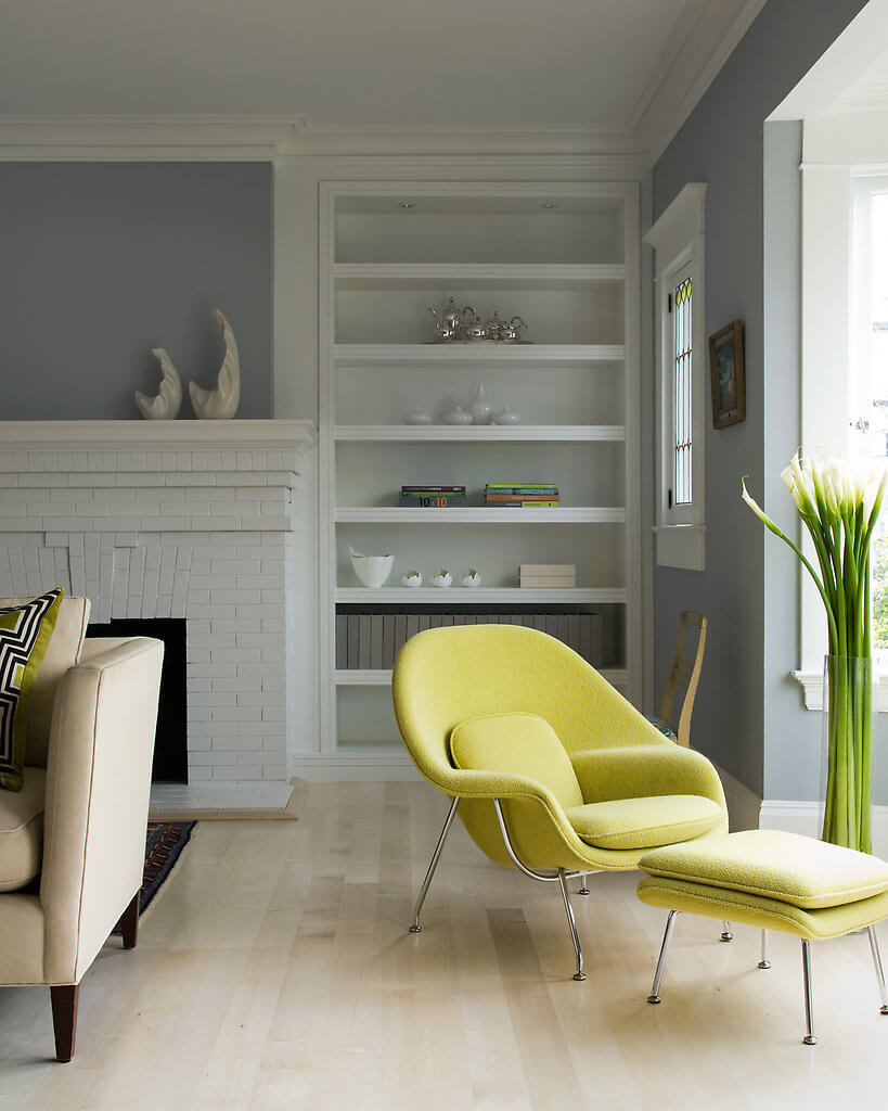 The elegant curves of this green-yellow armchair adds to the modernized retro feel of the home and pair perfectly with the standing floral arrangement. The original fireplace remains in place, but is given a new look with a touch of white paint.