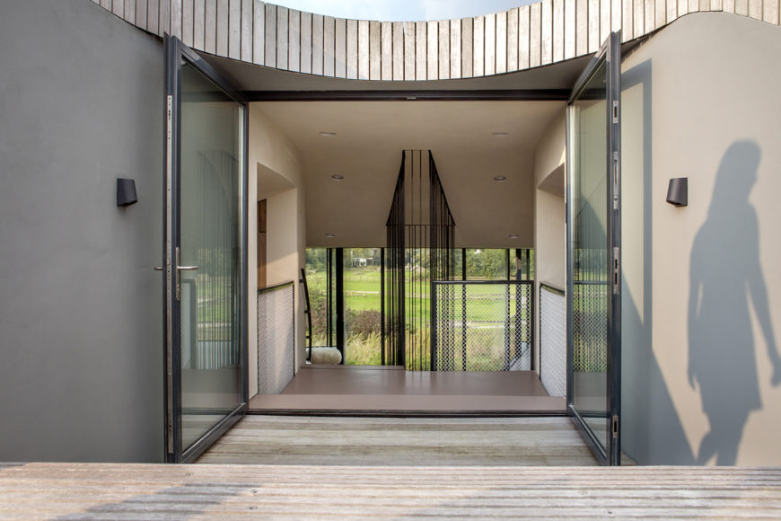 Outdoor walkways between the terraces and wings end in large glass double doors back to the interior. From this angle we can see the stairs leading down into one of the main living areas and the curve of the building's roof.