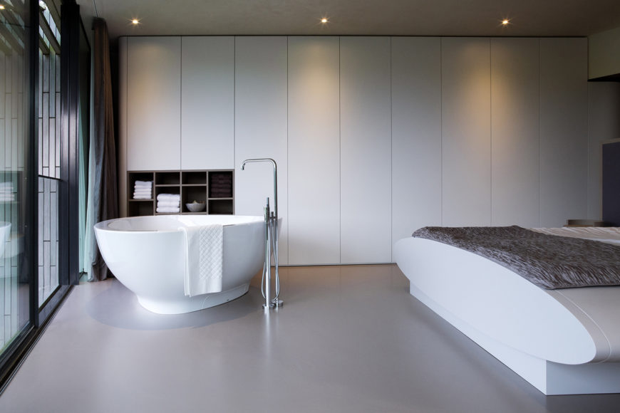 Near the rear of the home are the more private areas, which include this minimalist bathroom and bedroom combination. All along the rear wall are minimalist storage cabinets. The free-standing soaking tub sits near the sliding glass doors to one of the home's many terraces.