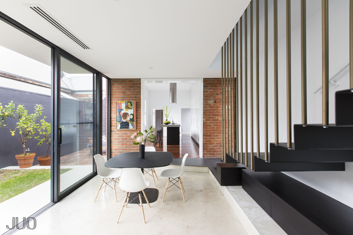 In the large open space running next to the courtyard, we see the small formal dining space next to a set of floating black metal stairs. Marble flooring, red brick walls, and contemporary furnishing combine for a richly textured appearance.
