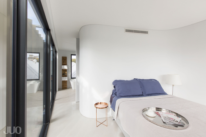 The master bedroom is awash in bright white tones, with sensuously curved walls and sleek flooring. Full height glazing is shaded by the set of aluminum louvers, at left.