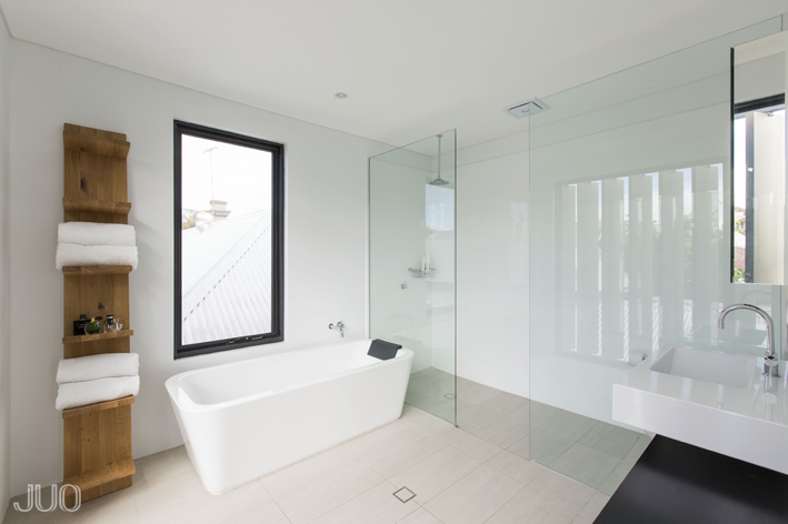 The primary bath is a feat of minimalist beauty, with large format tile flooring and a massive walk-in shower enclosed in glass. The white pedestal tub sits below a large window, with simple natural wood shelving at left.