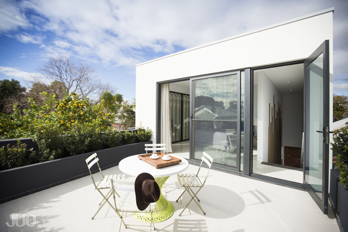 The modern addition features this rooftop patio extending from the primary bedroom.