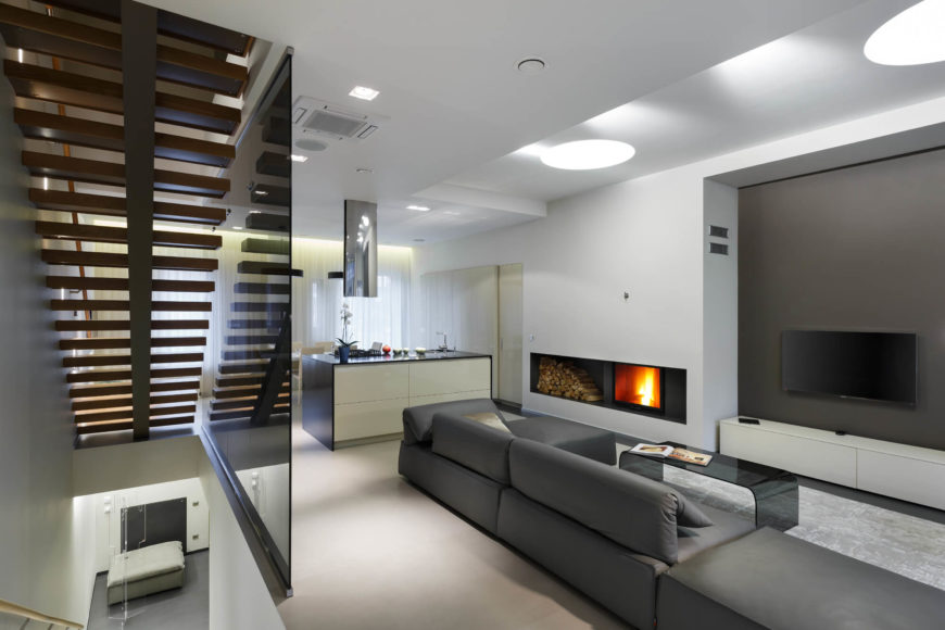 A tinted glass shade separates the stairs from the living area. The contemporary color scheme flowing throughout the room to create a chic atmosphere. A bright fireplace embedded into the wall provides a sense of comfort and intimacy.