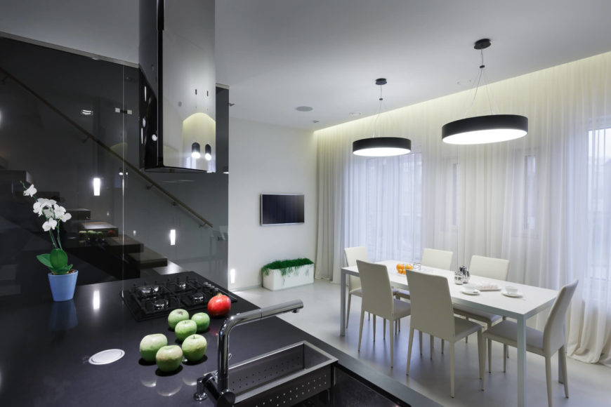An island holds the stove and sink, and still has lots of space for meal preparation. The dining table and chairs are monochromatic and correspond charmingly with the ongoing color scheme throughout the house. A waterfall of sheer white curtains covers the windows that line the wall.