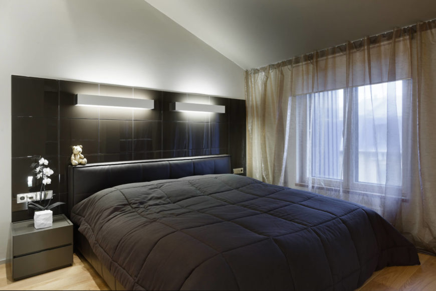 The master bedroom is sleek and attractive. A king-sized bed is the center of attention with a colossal headboard that provides storage space and soft light. Natural hardwood floor contrasts with the the dark color of the sheets and headboard.