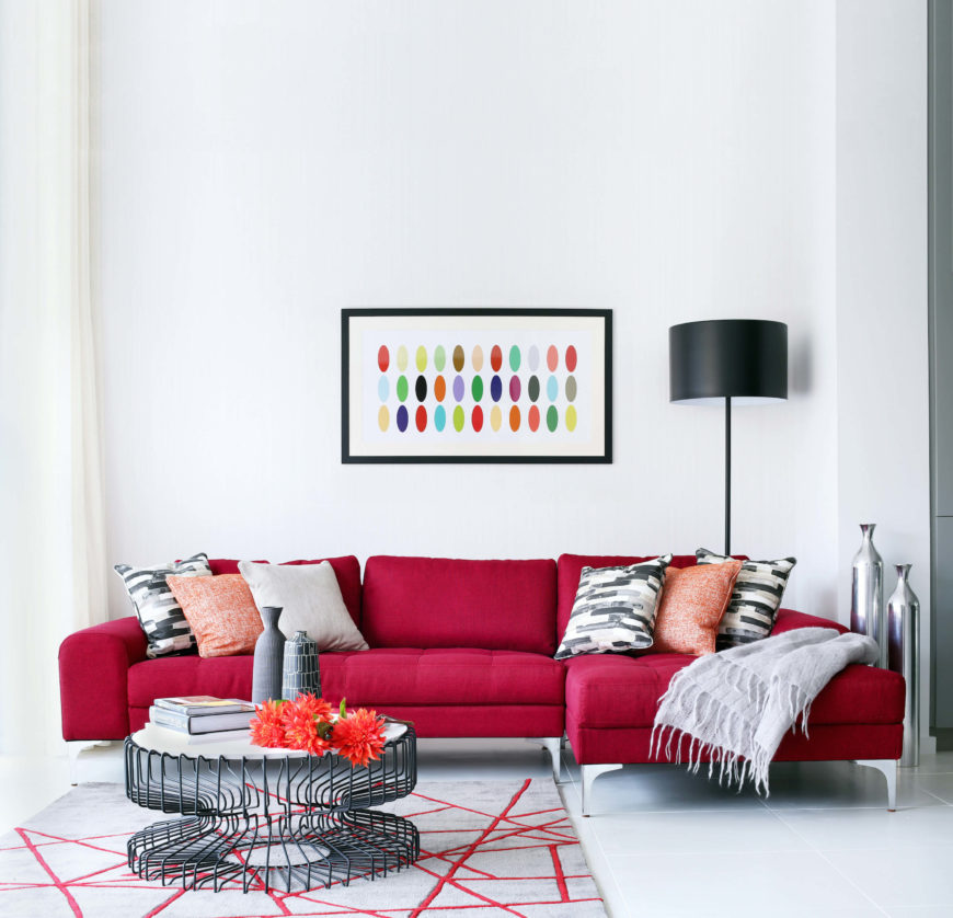 The family room bursts with color, centered on the rich red tone of the contemporary sectional, which is also reflected in the asymmetric area rug pattern. A lightly industrial coffee table boasts a wire frame and white surface, contrasting with the sleek white flooring and walls.