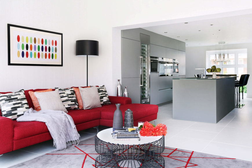 The open-plan family room and kitchen space reveals a dichotomy between bright colors and sleekly minimalist design.