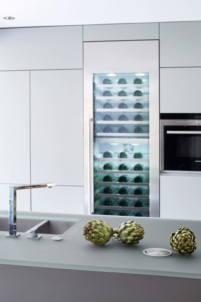 An immense built-in wine cooler is seen here flanked by the sleekly minimalist cabinetry, free of any visible hardware. The smoked glass countertop makes for a glowing appearance over the metallic island, with ultra-modern sink design at left.
