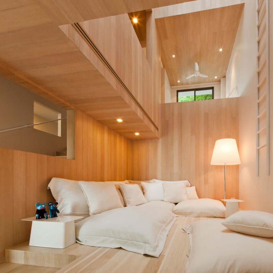 At the bottom of the void we see this relaxation space, spread casually with low-slung white cushioned seating and matching modern tables. Above, the open space hints toward the open-plan floors above.