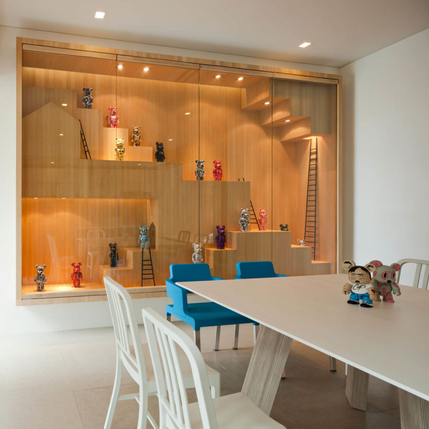 Here we see the elaborate display cabinet, the centerpiece of the home and a reflection in miniature of the structure. The Be@rbrick figures adorn every step within the rich wood display, hinting at the style of the larger home itself.