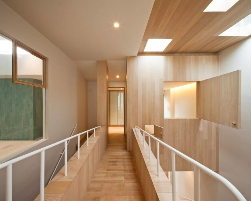 The upper level, overlooking the massive vertical space, spans the gap with this elegant catwalk flanked by white rails. Small cubby-style openings adorn the walls throughout.