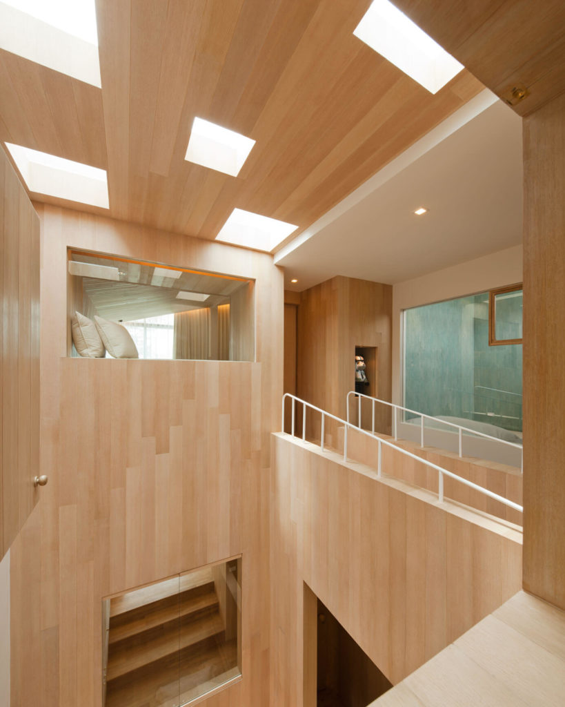 From here we see openings at various levels within the vertical open space. Glass panels and doorways allow glimpses into bedrooms and bathrooms.
