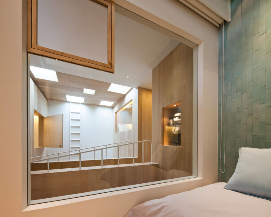 Within this bedroom, we see through a massive interior window over the central void, highlighting the intricate interplay of textures and hardware. Natural wood, white walls, glass, and metal intersect in every major space.