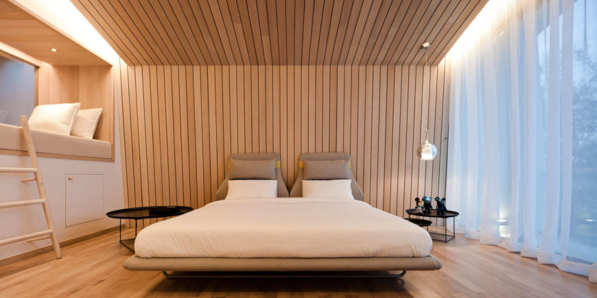 The master bedroom, at the top of the home, is wrapped in rich hardwood panels from top to bottom, with a full height window at right and small loft space overlooking the central void at left.
