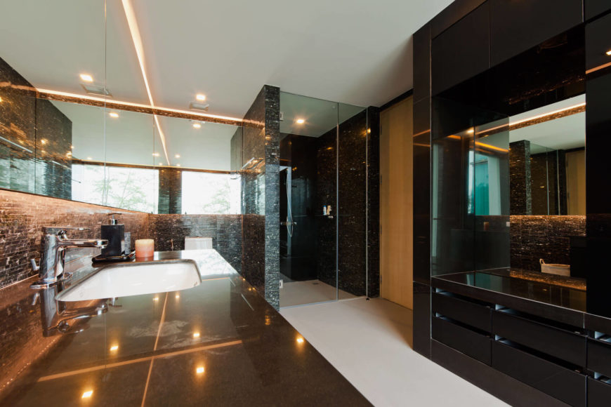 The master bath stands in high contrast with the rest of the home, adorned in rich black tile, sandwiched between white flooring and ceiling. A micro-tile backsplash runs toward the walk-in shower, enclosed in class.