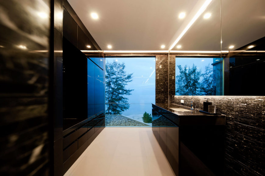 Even the bathroom enjoys expansive natural views, with full height glazing allowing for looks over the beach and ocean. Intricate embedded lighting informs the ceiling and wraps the large mirror.