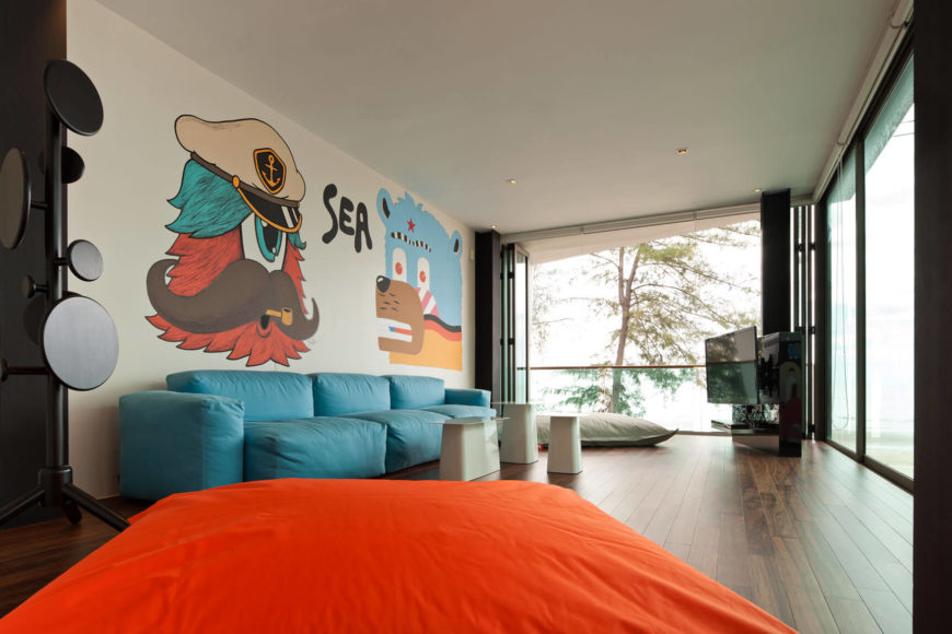 This open living room space stands over a rich, dark hardwood floor, with bold minimalist splashes of color throughout. Full height glazing and retractible glass panels open the area to the outdoors and surrounding patio.