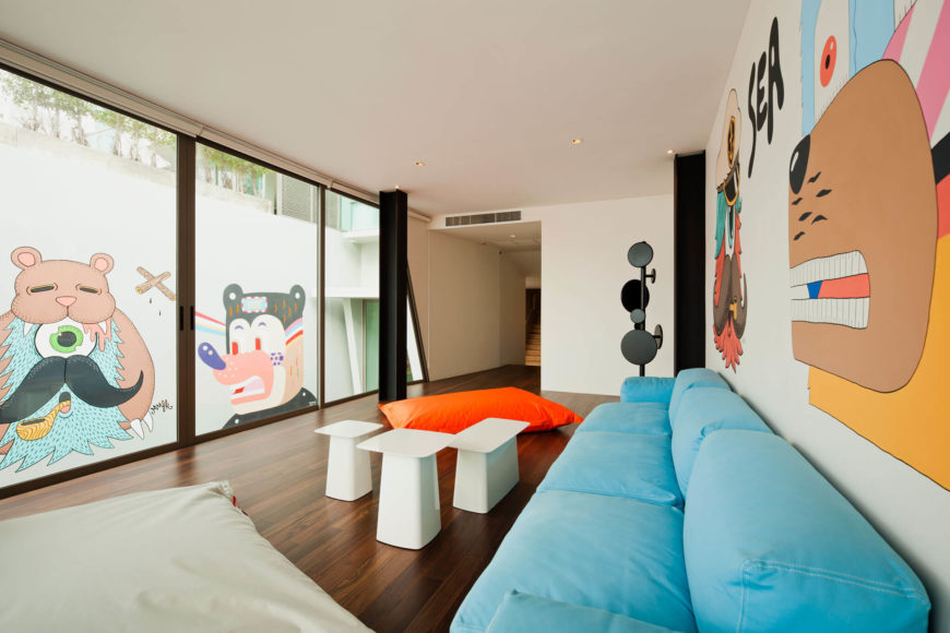 The thematic graffiti adorns large spaces throughout the home, adding personality and detail to the sleekly modern space. The sky blue sofa and set of pure white coffee tables are complemented by black I-beams and white walls.