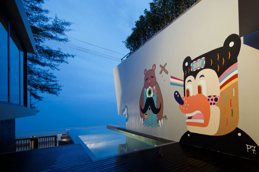 Outside, we see more of the gorgeous artwork on an exterior wall, overlooking an infinity pool on the edge of the hardwood deck.