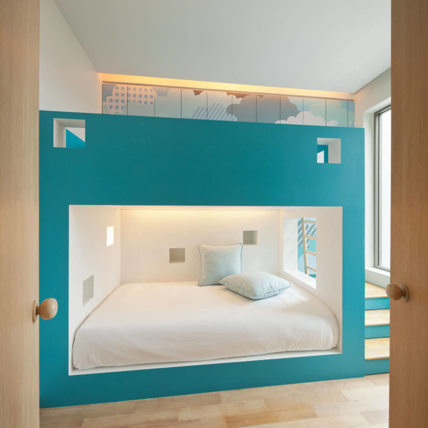 This playful room is perfect for kids, with a bright blue and white mixture adorning the natural wood materials. The room centers on a massive bunk bed-like structure.