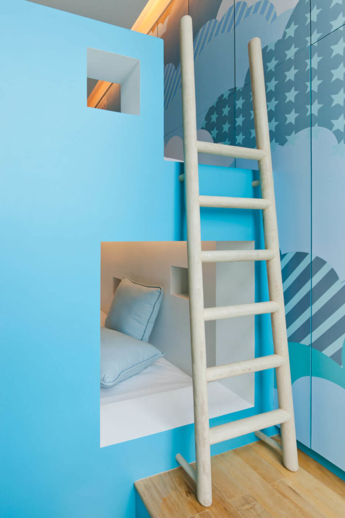 This built-in ladder leads to an upper loft-style bunk within the room, mirroring the intricate block-like structure of the wider home itself.