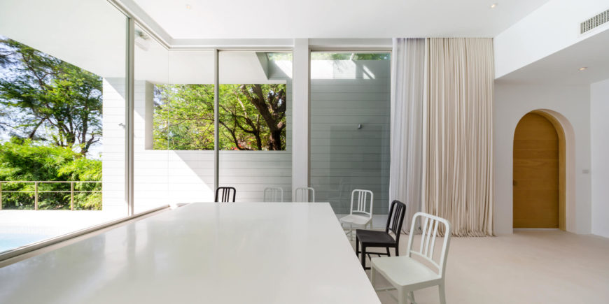 Here's the expansive dining room, centered on a massive white table. The social spaces in the home are defined by white walls and full height glazing. The pool area can be seen at left.