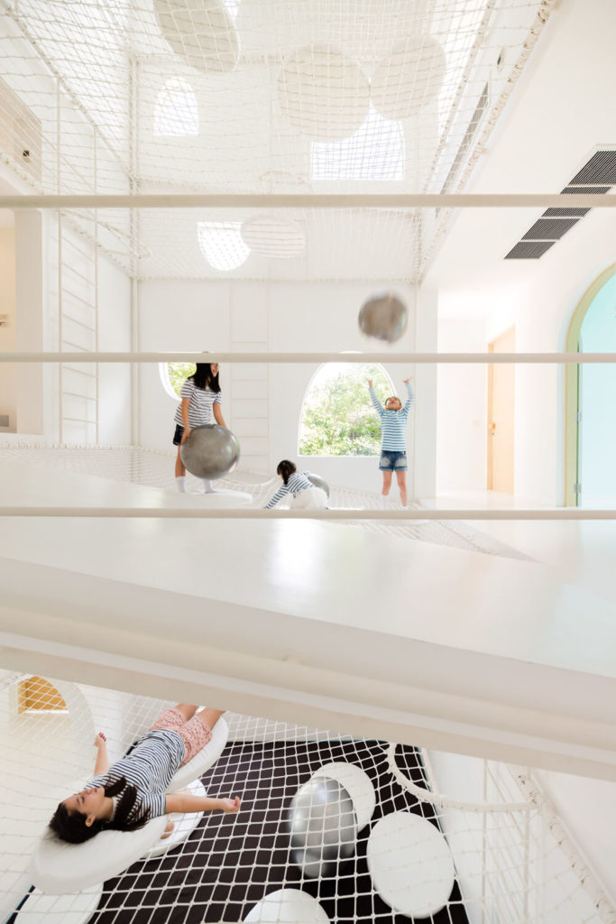 """This split-level view shows how the normal rules of home architecture simply do not apply within the playful vertical center of this home. A sloped hall wraps one of the angled net """"floors,"""" as we see children occupying levels above and below."""