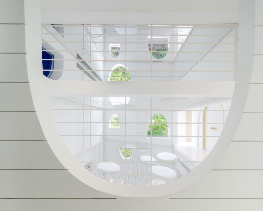 Looking into the vertical space from within the proper upper floor, we see the playful array of arched and curved window openings, as well as an adjacent hallway open entirely to the needed space.