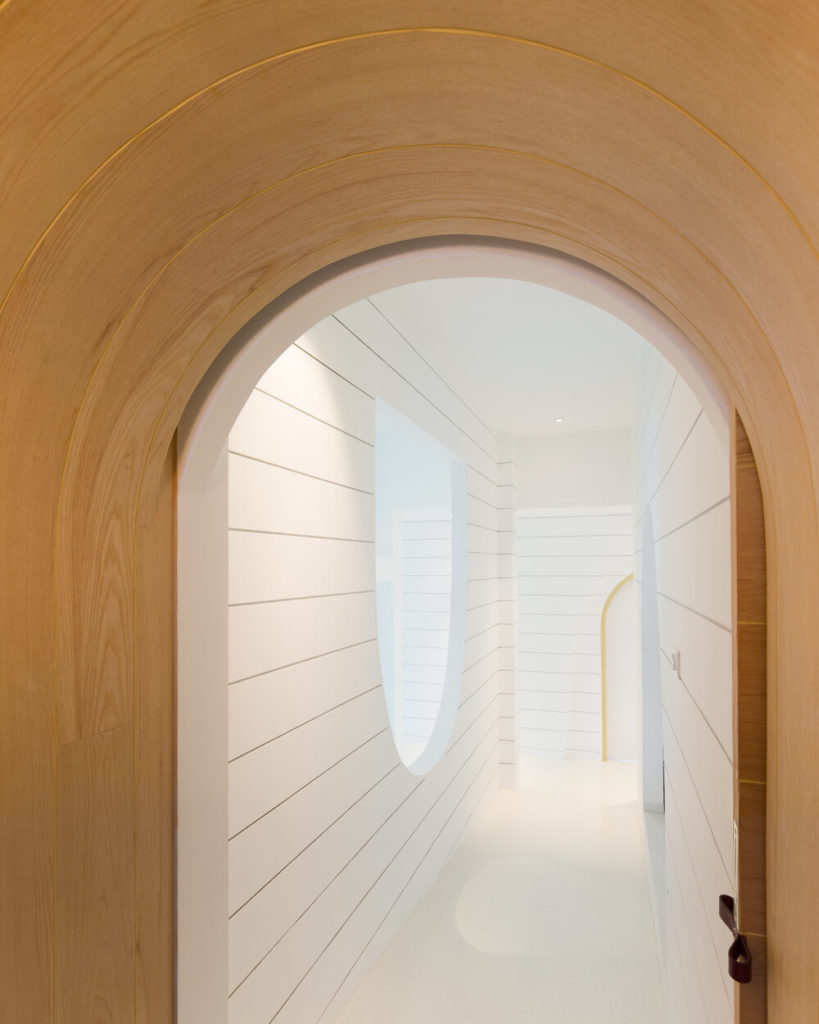We leave you with one last glimpse into the white dominated social space of the home. The intricate curved wall cutouts define the interplay of the structure as much as the central net-filled space.