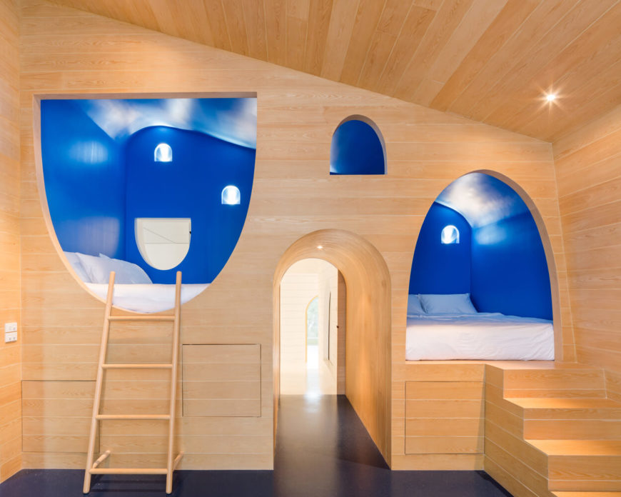 Playful wooden bedroom with an open archway features vibrant blue elevated bed cubbies lined with a ladder and a staircase.