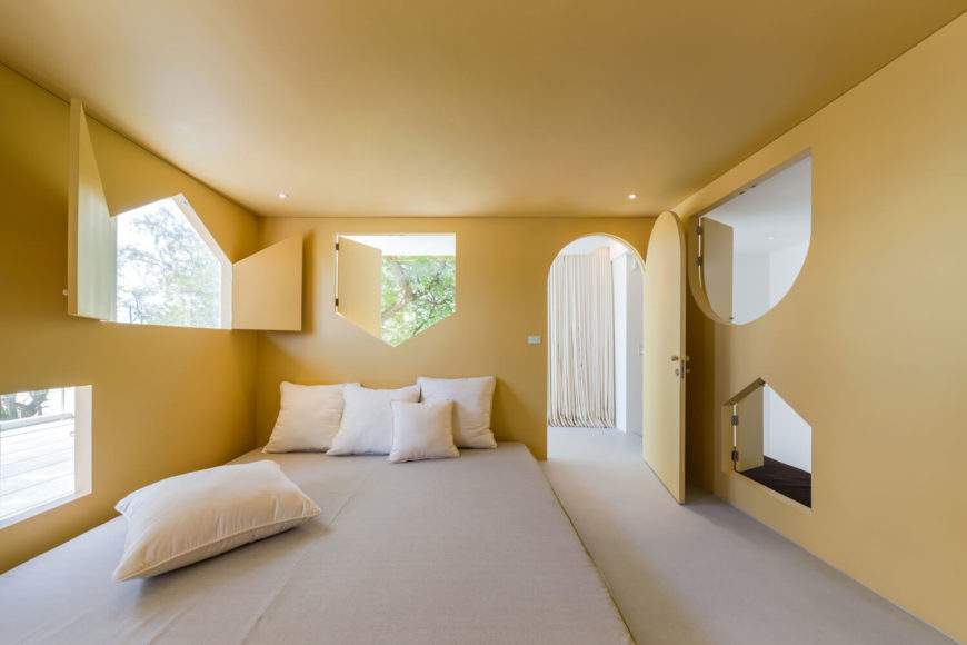 Mustard yellow master bedroom showcases various shaped windows and an arched door. It has a gray floor bed accented with white pillows.
