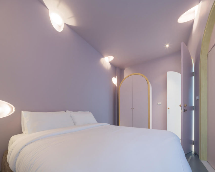 Purple master bedroom offers a white bed and arched wardrobe lined with gold. It is surrounded by scattered wall lights that illuminate the room.