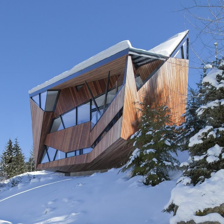From down the slope we can see the way the unique shape of this wood and glass home seems to perch precariously on the snow-covered slope at the top of the valley.