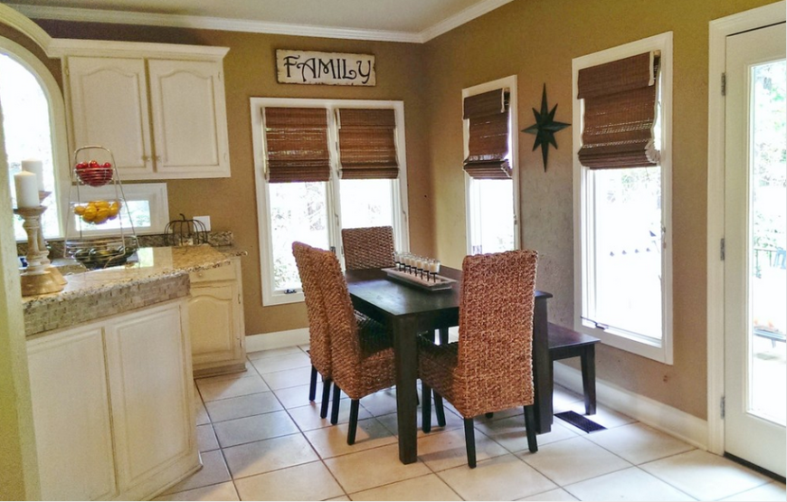The kitchen, in contrast with the living room spaces we've seen, is wrapped in bright walls over white large format tile flooring. An abundance of windows allows natural light to play on the granite countertops and dark stained wood dining table.