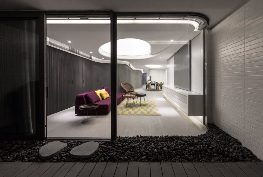 The modernized living room can be viewed through curved exterior glazing revealing sharp Scandinavian furniture and smooth rounded walls. Beyond the door lays a pool of black pebbles to separate the smooth flooring of the home from the balcony outside.