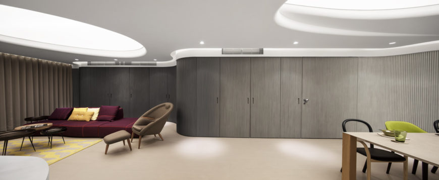 A seamless flow of gun metal grey walls can be opened to reveal the pantry, powder room, and various closets. Large swirling ceiling lights create a soft tranquil glow throughout the rooms.